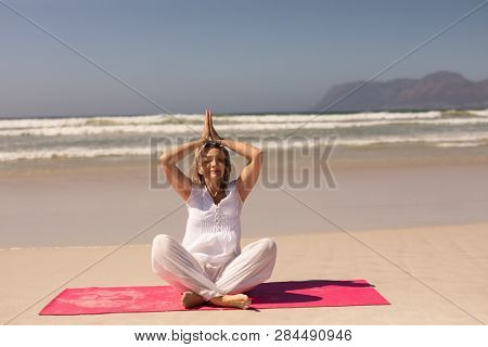 Front view of active senior woman meditating in prayer position at beach with mountains in the background