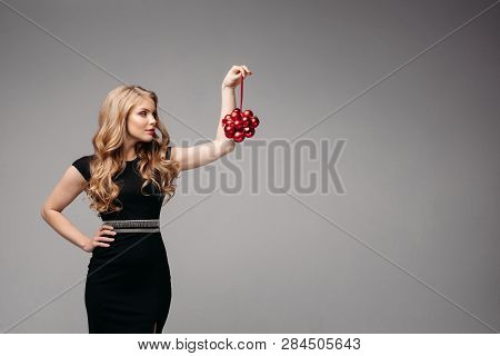 Side view of sexy woman keeping in hand adornment in studio poster