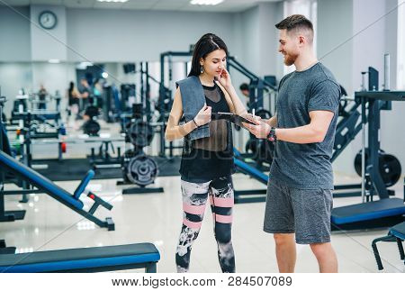 Fitness Woman Exercising With Fitness Trainer In Gym. Personal Fitness Instructor. Personal Training