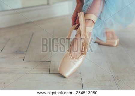 Hands Of Ballerina In Blue Tutu Skirt Puts On Pointe Shoes On Leg In White Light Hall. Young Classic