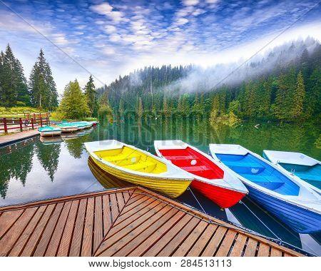 Boats On Majestic Mountain Lake Lacul Rosu Or Red Lake Or Killer Lake. Splendid Foggy Summer Scene O