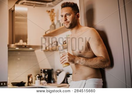 Attrctive Young Man With Bare Torso Holding Hand Orange Juice, Looking Out The Window And Smiling Wh