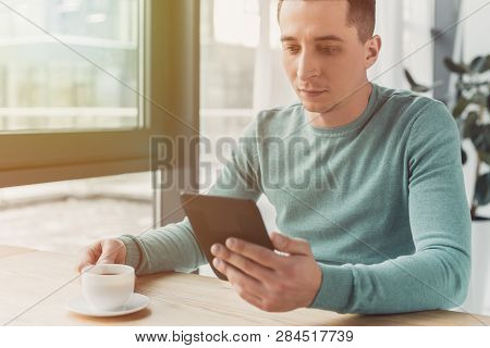 Handsome Man Studing With Ebook And Holding Cup Of Tea At Home