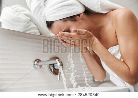 Close up of a beautiful young woman with towel on her head standing at the bathroom, washing her face