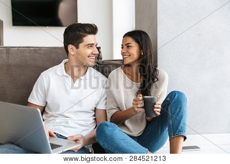 Happy young couple sitting on a floor at home, using laptop computer