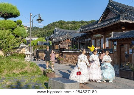 Jeonju, South Korea - September 2018: Tourists In Hanboknam (korean Traditional Dress) Walking Pass