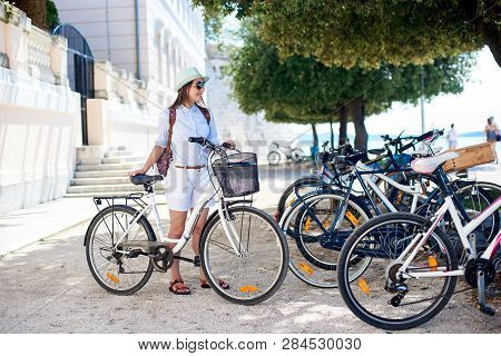Attractive Smiling Girl In Sunglasses, White Shorts, Blouse And Hat With A Bicycle In Shadow Of Palm