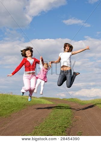 two women and one girl jump outdoor