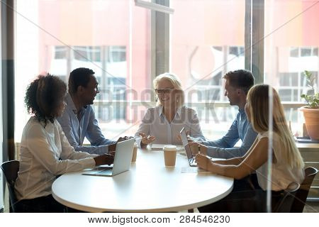 Five Diverse Businesspeople Sitting In Boardroom And Negotiating