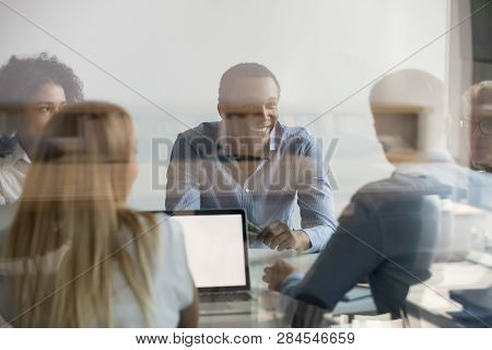 Businesspeople Negotiating At Boardroom View Through Glass Wall