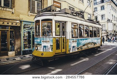 Lisbon, Portugal - April 19, 2014: Street View With Famous Old Tourist Tram Full Of People During Th