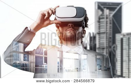 Young Handsome Businessman In Virtual Helmet Against Cityscape Background