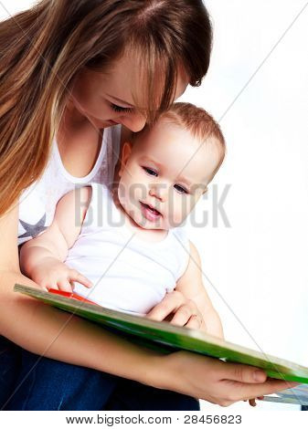 young attractive mother reading a book to her daughter