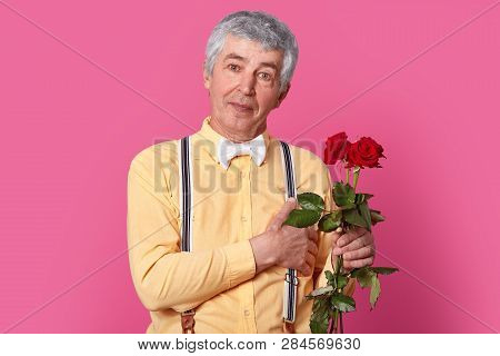 Horizontal Shot Of Impressed Grey Haired Elderly Man In Formal Fashionable Clothes, Keeps Hand Near