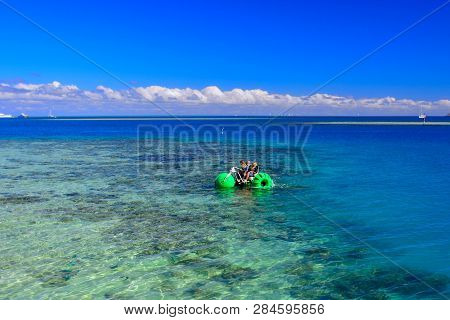 A Father And Two Kids Riding A Water Bike (or Trike) Over Bright Blue Waters And Coral Reefs On A Su