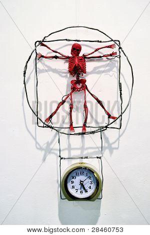 Red Toy Skeleton, Which Hangs Over A Mechanical Alarm Clock - A Parody Of Leonardo Da Vinci Work