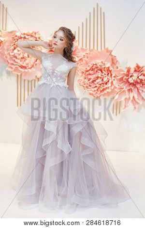 Beautiful Bride In An Expensive Wedding Dress In Presence Of Large Artificial Flowers. Girl In White