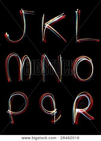 the letters, j,k,l,m,n,o,p,q, r written in the dark with torches and lasers