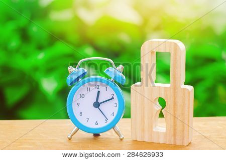 Blue Alarm Clock And Padlock. Non-durable Protection Time-tested Protection And Stability. Saving Ti