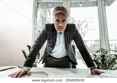 Tall Grey-haired Adult Manager In Eyeglasses Looking Irritated