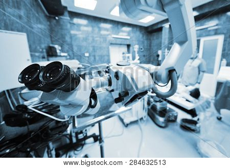 surgical microscope on the background of modern neurosurgical operating room and doctors poster