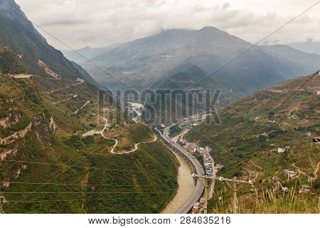 Highway Passes In A Gorge In The Mountains Along The River, Heng River, Yunnan Province, China