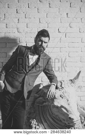 Man With Beard And Mustache On White Brick Wall Background. Hipster With Strict Face In Suit Abuts O