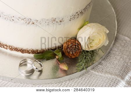 Closeup Picture About A Detail Of White Wedding Cake With Ornaments, With White Gold Wedding Bands