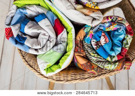 Patchwork And Fashion Concept - Close-up On Three Colorful Quilts Rolled Into A Tube And Laid In A W