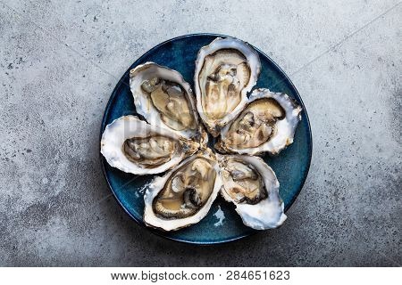 Set Of Half Dozen Fresh Opened Oysters In Shell Served On Rustic Blue Plate On Gray Stone Background
