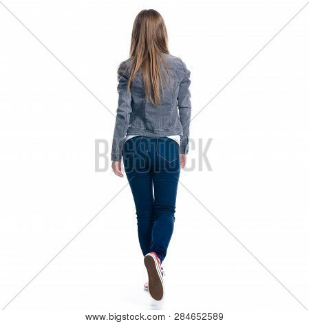 Woman In Jeans Goes Walking On White Background. Isolation, Back View