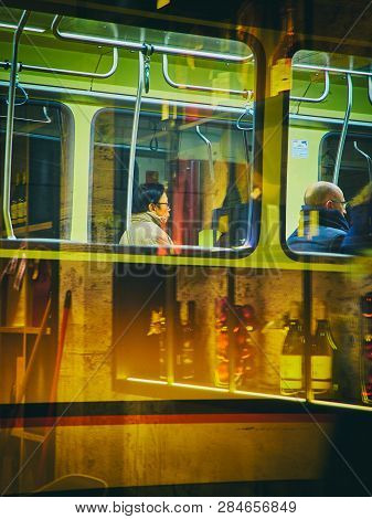 Milan, Italy - December 29, 2018. A Tram Transporting A Oriental Men In Milan At Night. Lombardy, It