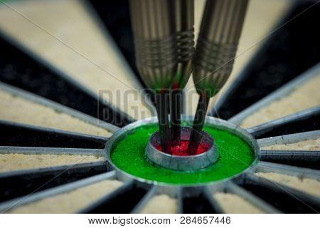Macroshot Of Three Darts In The Bulls Eye Of A Dartboard