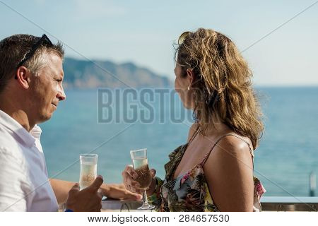 Couple Drinking Champagne Near The Sea On There Holiday