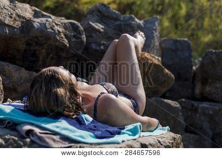 Woman Relaxed Sunbathing On The Rocks In Bikini
