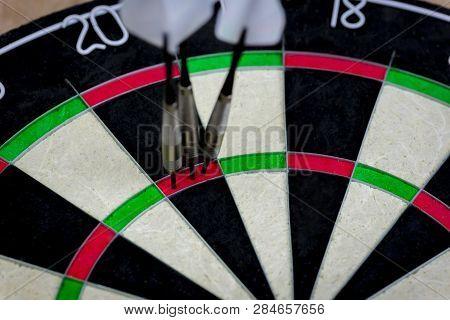 Dart Board With Three Darts In The Triple Twenty Area.