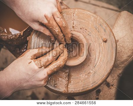 Rotating Potters Wheel And Clay Ware On It Taken From Above. A Sculpts His Hands With A Clay Cup On