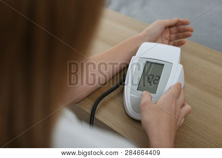 Woman Checking Blood Pressure With Sphygmomanometer At Table Indoors, Closeup. Cardiology Concept