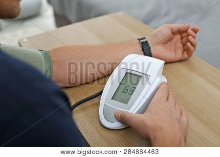 Man Checking Blood Pressure With Sphygmomanometer At Table Indoors, Closeup. Cardiology Concept