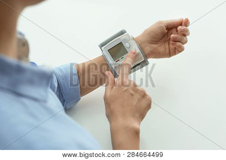 Woman Checking Blood Pressure With Sphygmomanometer At Table, Closeup. Cardiology Concept