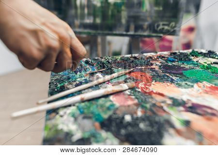 Brushes On A Palette Of Oil Paint, A Hand Of The Artist With A Knife Palette Takes A Paint. Hands Of