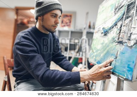 Young Concentrated Artist, Sitting In A Studio On A Chair Near The Easel With The Host, Applying An