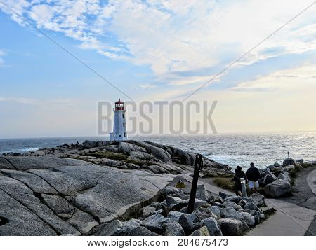 Peggys Cove, Nova Scotia, Canada - July 7th, 2014: Visitors walking towards Peggys Point Lighthouse, also known as Peggys Cove Lighthouse, an active lighthouse and an iconic Canadian image. poster