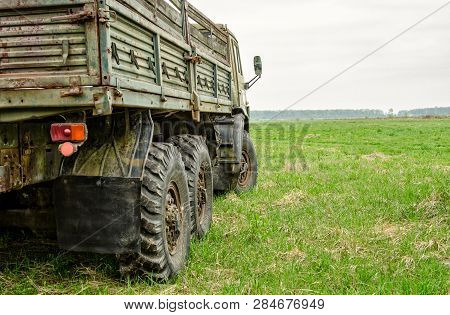 Close Up Of A Rear Right Side Of Military Truck On Proving Ground, Green Field, Overcast