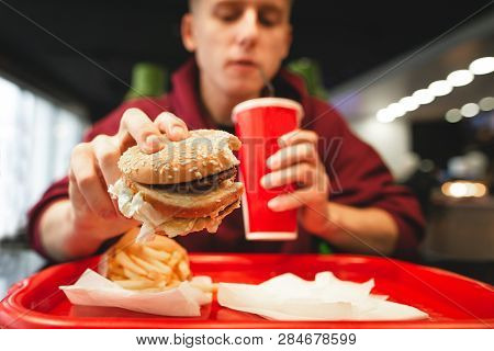 Young Man Dishes Fast Food At A Fast Food Restaurant. Man Holds A Burger In His Hand, Drinking A Col
