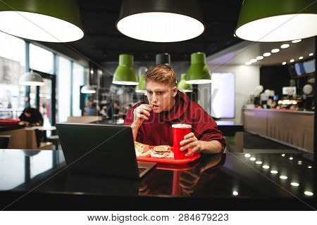 Portrait Of A Young Man Eating Fast Food At A Restaurant And Using A Laptop. Concentrated Freelancer
