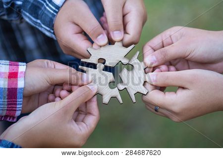 People Helping In Assembling Puzzle, Cooperation In Decision Making, Team Support In Solving Problem