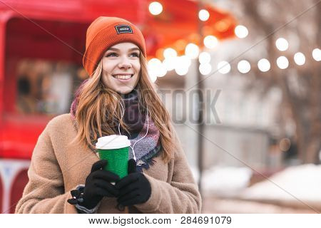 Beautiful Woman Wearing A Coat Standing In The Street With A Cup Of Coffee In Her Hands, Looking On
