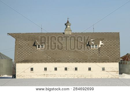 A Old Barn Probably Used For Storage With A Cupola And A Weather Vane On Top And Dormer Windows Buil