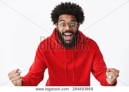 Studio shot of surprised and thrilled african american guy clenching fists in joy and amazement popping eyes and smiling excited reacting to unexpected great news, winning, achieving prize poster
